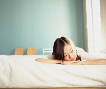 ベッドでうつ伏せになる女性