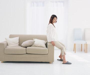 ソファーの肘掛けに腰かける女性